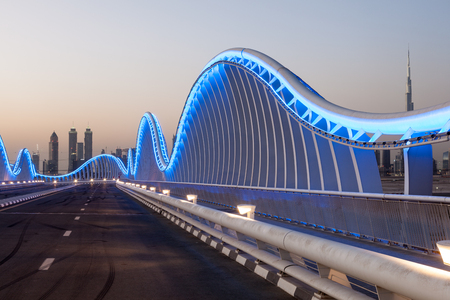 Wave shaped Meydan Bridge in Dubai blue illuminated at night. United Arab Emirates