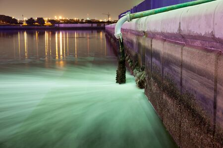 river       water: Sewage pipe discharging water into a river at night. Dubai Creek, UAE Stock Photo