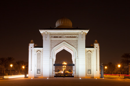 sharjah: SHARJAH, UAE - DEC 17: University City of Sharjah Entrance Gate at night. December 17, 2014 in Sharjah, UAE