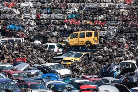 scrapyard: Stacked wrecked cars going to be shredded in a recycling plant Stock Photo