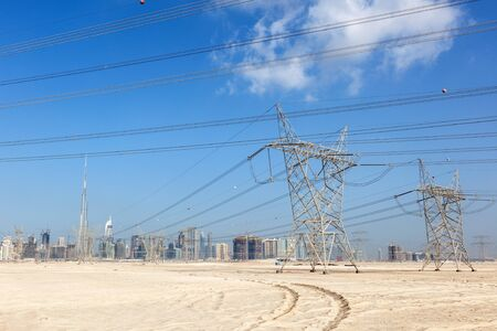 electricity pole: Skyline of Dubai with high voltage power supply lines