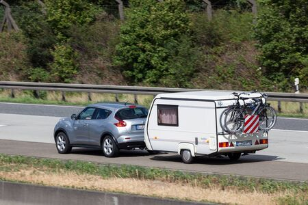 autobahn: FRANKFURT, GERMANY - JULY 21: Nissan Juke with with a small caravan travelling at the A5 highway in Germany. July 21, 2015 in Frankfurt Main, Germany