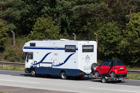 autobahn: FRANKFURT, GERMANY - JULY 26: Mobile home with the Smart ForTwo on trailer moving south on the highway A5. July 26, 2015 in Frankfurt Main, Germany Editorial