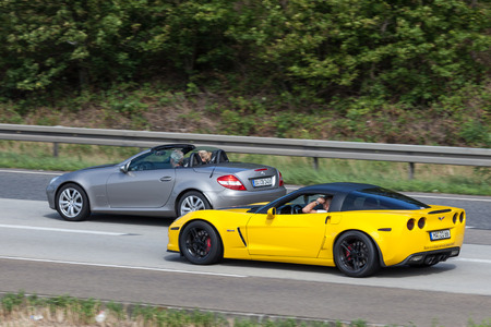 corvette: FRANKFURT, GERMANY - JULY 26: Yellow Chevrolet Corvette and silver Mercedes Benz Roadster moving fast on the highway A5 near Frankfurt. July 26, 2015 in Frankfurt Main, Germany