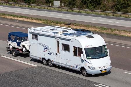 FRANKFURT, GERMANY - JULY 26: Frankia Luxury Class mobile home with a trailer moving south on the highway A5. July 26, 2015 in Frankfurt Main, Germany