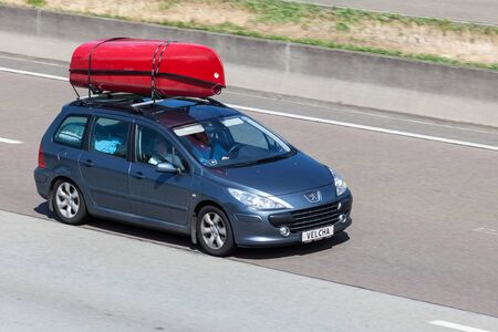 station wagon: FRANKFURT, GERMANY - JULY 26: Peugeot 307 Station Wagon with kayaks on the roof moving fast on the highway A5 towards south. July 26, 2015 in Frankfurt Main, Germany
