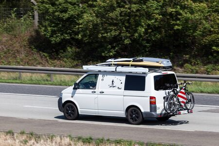 t5: FRANKFURT, GERMANY - JULY 26: Volkswagen van T5 with surfing boards on the roof moving fast on the highway A5 towards south. July 26, 2015 in Frankfurt Main, Germany