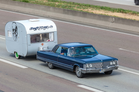 coupe: FRANKFURT, GERMANY - JULY 26: Classic American coupe with an old caravan moving on the highway A5 near Frankfurt. July 26, 2015 in Frankfurt Main, Germany