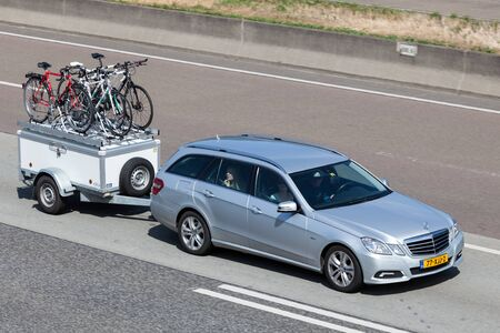 station wagon: FRANKFURT, GERMANY - JULY 26: Mercedes Benz W212 Station Wagon with a trailer moving fast on the highway A5 towards south. July 26, 2015 in Frankfurt Main, Germany Editorial