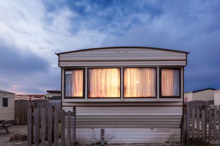 Old vacation home trailer illuminated at dusk. Trailer park in Holland, Netherlands Editorial