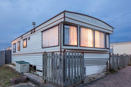 remolque: Acoplado viejo casa de vacaciones iluminado en la oscuridad. Parque de casas rodantes en Holanda, Países Bajos Editorial