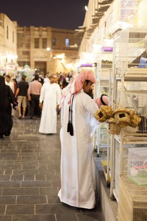 thoub: DOHA, QATAR - NOV 19: Qatari man shopping at the traditional market Souq Waqif. November 19, 2015 in Doha, Qatar, Middle East Editorial