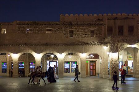thoub: DOHA, QATAR - NOV 19: People at the traditional market Souq Waqif at night. November 19, 2015 in Doha, Qatar, Middle East