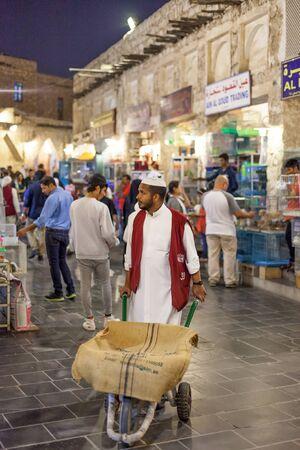 carretilla de mano: DOHA, QATAR - 19 DE NOVIEMBRE: Hombre de Qatar con una carretilla de mano en el mercado tradicional de Souq Waqif. 19 de de noviembre de, 2015, en Doha, Qatar, Oriente Medio