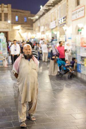 thoub: DOHA, QATAR - NOV 19: Expatriate man at the traditional market Souq Waqif. November 19, 2015 in Doha, Qatar, Middle East