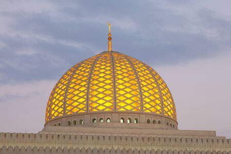 Cupola of the Sultan Qaboos Grand Mosque illuminated at dusk. Muscat, Oman, Middle East