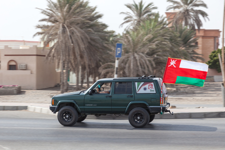 oman: MUSCAT, OMAN - NOV 24: Car with a national flag of Sultanate of Oman. November 24, 2015 in Muscat, Oman, Middle East Editorial