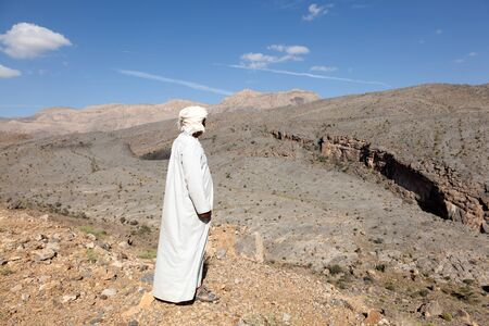 tourist guide: GHUL, OMAN - NOV 26: Omani Tourist guide looking at the Wadi Ghul (Grand Canyon). November 26, 2015 in Wadi Ghul, Sultanate of Oman, Middle East Editorial