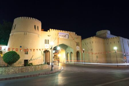 autos: NIZWA, OMAN - NOV 25: Gate to the old town of Nizwa illuminated at night. November 25, 2015 in Nizwa, Sultanate of Oman, Middle East