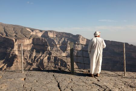mountainscape: GHUL, OMAN - NOV 26: Omani Tourist guide looking at the Wadi Ghul (Grand Canyon). November 26, 2015 in Wadi Ghul, Sultanate of Oman, Middle East Editorial