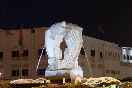 muttrah: MUSCAT, OMAN - NOV 28: Fish fountain at a roundabout in Muttrah illuminated at night. November 28, 2015 in Muscat, Sultanate of Oman, Middle East