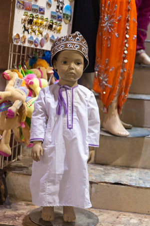 muttrah: Traditional Omani dress - Kuma hat and Dishdasha shirt on a child mannequin. Muscat, Sultanate of Oman, Middle East