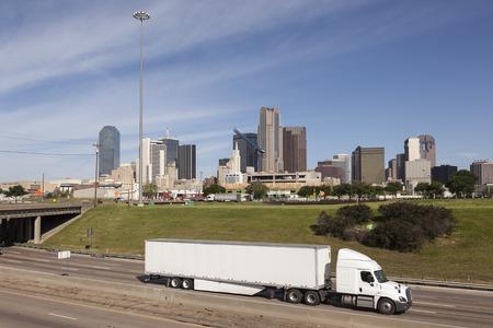 Vrachtwagen op de snelweg met Dallas downtown skyline op de achtergrond. Texas, Verenigde Staten