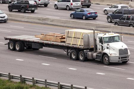 mack: DALLAS, USA - APR 8: Flatbed semitrailer freight truck on the highway in United States. April 8, 2016 in Dallas, Texas, USA