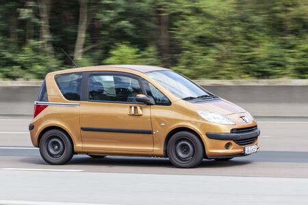mpv: FRANKFURT, GERMANY - JULY 12, 2016: Peugeot 1007 Mini MPV with sliding doors driving on the highway in Germany