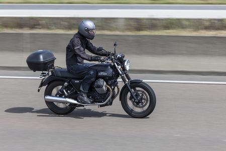 motociclista: FRANKFURT, Alemania - 12 de julio, 2016: Motorista en la motocicleta de Moto Guzzi V7 conducción en la carretera en Alemania
