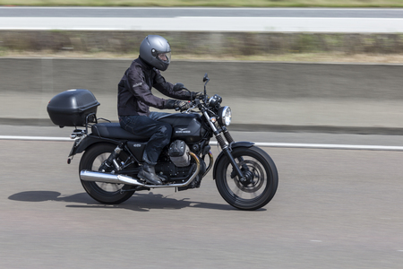 motorcyclist: FRANKFURT, GERMANY - JULY 12, 2016: Motorcyclist on the Moto Guzzi V7 motorcycle driving on the highway in Germany