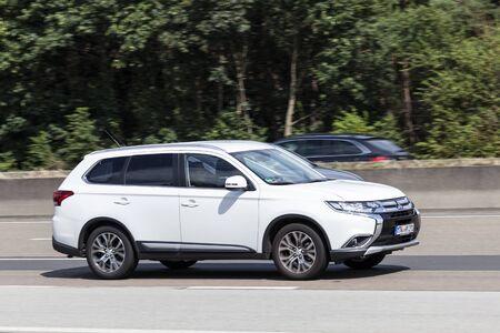outlander: FRANKFURT, GERMANY - JULY 12, 2016: Third generation Mitsubishi Outlander on the highway in Germany