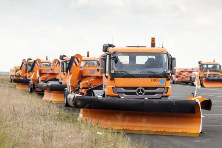 plough: FRANKFURT, GERMANY - JULY 24, 2016: Orange Mercedes snow plough trucks waiting for winter at the Frankfurt International Airport