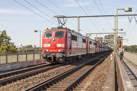 db: COLOGNE, GERMANY - AUG 7, 2016: Red Deutsche Bahn train at the South Bridge in Cologne, North Rhine-Westphalia, Germany
