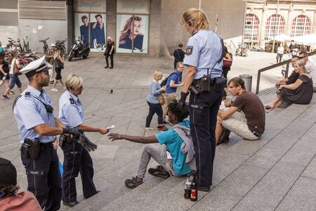 rampage: COLOGNE, GERMANY - AUG 7, 2016: Policewomen and a policeman checking pasport of a drunk refugee in front of the central station in Cologne, Germany Editorial