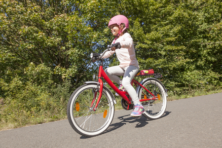 Adorable kid girl with pink helmet riding a bicycle photo