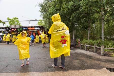 macintosh: GUNZBURG, GERMANY - AUG 18, 2016: Family wearing yellow ponchos at the Legoland Deutschland in Guenzburg, Baden Wurtemberg, Germany Editorial