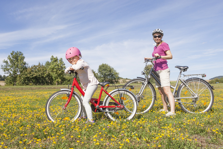 Family with bikes enjoying summer day in a park photo