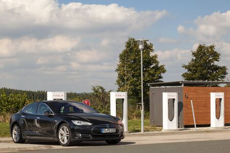 supercharger: WILNSDORF, GERMANY - SEP 1, 2016: Tesla Model S electric car being charged at the Tesla Supercharger station Editorial