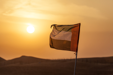National flag of the United Arab Emirates backlit at sunset