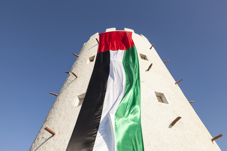 Old tower in Abu Dhabi decorated with huge UAE flag for the celebration of 45th National Day