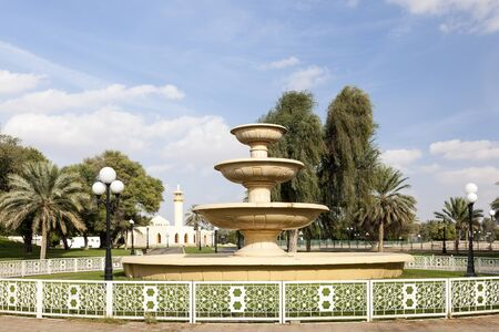 AL AIN, UAE - NOV 29, 2016: Fountain and mosque at the Hili archaeological park in Al Ain. Emirate of Abu Dhabi, United Arab Emirates Stock Photo