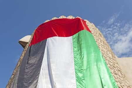 Old tower decorated with the UAE national flag. Dubai, United Arab Emirates, Middle East