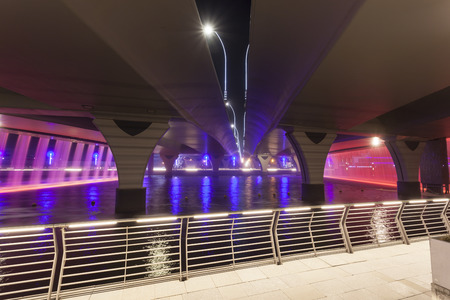 Dubai Water Canal and Waterfall under the Sheikh Zayed Road bridge at night. United Arab Emirates, Middle East