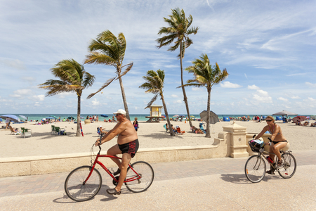 ciclovia: Hollywood Beach, Fl, USA - March 13, 2017: Bicycle rider at the Hollywood Beach Broad Walk on a sunny day in March. Florida, United States Editorial