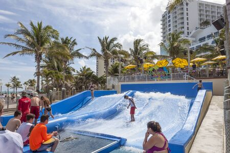 Hollywood Beach, Fl, USA - March 13, 2017: People are surfing on the FlowRider surf simulator in Hollywood Beach broadwalk. Florida, United States