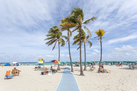 Hollywood Beach, Fl, USA - March 13, 2017: People relaxing under palm trees at the Hollywood Beach on a sunny day in March. Florida, United States