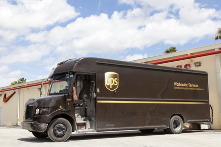 Homestead, Fl, USA - March 17, 2016: United Parcel Service delivery truck delivering packages to the stores in a mall. Florida, United States