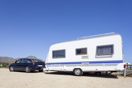 Car with a caravan parked at the mediterranean coast in Spain