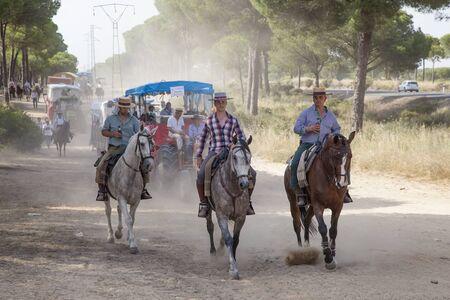 camino: El Rocio, Spain - June 1, 2017: Pilgrims on horseback in  traditional spanish dress on the road to El Rocio during the pilgrimage Romeria 2017. Province of Huelva, Almonte, Andalusia, Spain